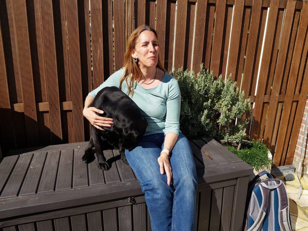 Zwarte labrador Tarka zit naast Debby op een kist in de tuin