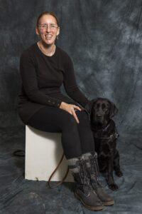 Zwarte labrador Tarka zit naast Debby op een verhoging